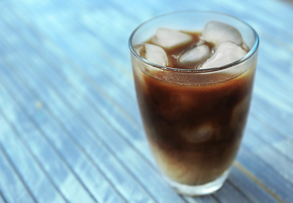 Glass of iced coffee on wooden background