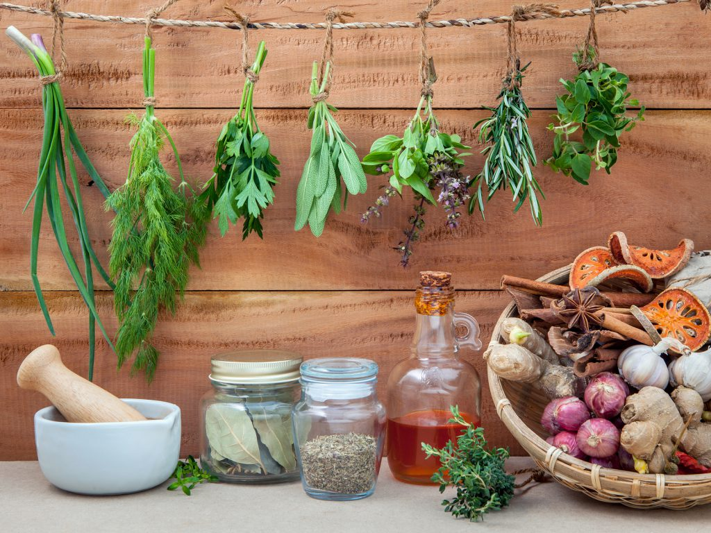 Assorted hanging herbs parsley oreganosagerosemarysweet basildillspring onion and set up with dry and fresh thyme bay leavessesame oil cinnamon star anise for seasoning concept on rustic old wooden background.